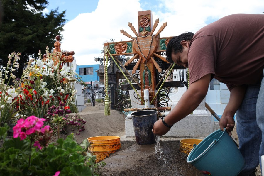 My cousin Cesar sprinkles water on our Abuelita's grave in preparation for Dia De Lose Muertos. Photo: Alex Washburn