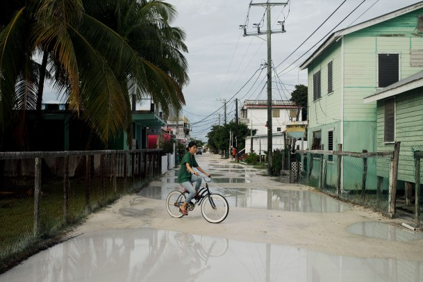 A resident weaves through puddles on Caye Caulker as storm clouds start to clear. Photo: Alex Washburn