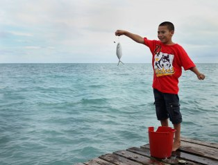 A young boy shows off his catch to his older brother. I hung out with these kids for over a half an hour and they caught two fish while the adults on the pier came up empty handed. Photo: Alex Washburn