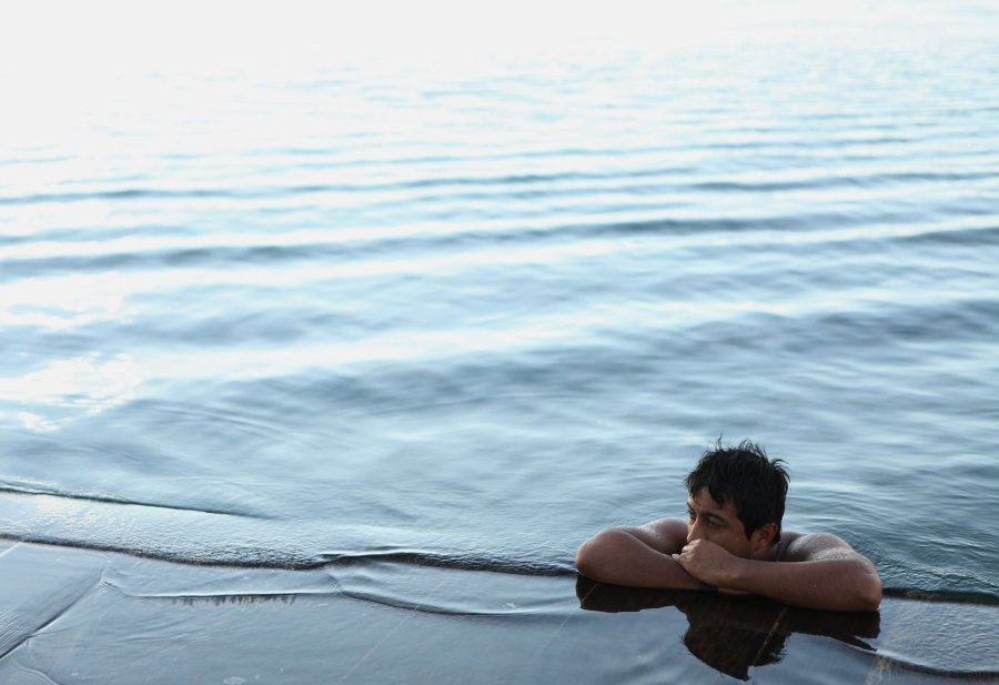 Flores Guatemala is a tiny island in the middle of Lake Peten Itza. The residents have a habit of jumping in the water at random times - swimming for just a few minutes and then going back to whatever they were doing. This gentleman went for a really long swim and is resting for a moment while his girlfriend waits on the shore. Photo: Alex Washburn