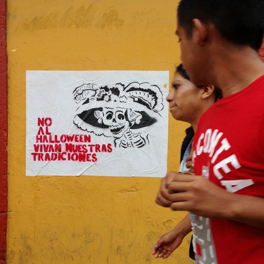 People walk past graffiti protesting the Halloween-ization of Dia De Los Muertos. Photo: Alex Washburn