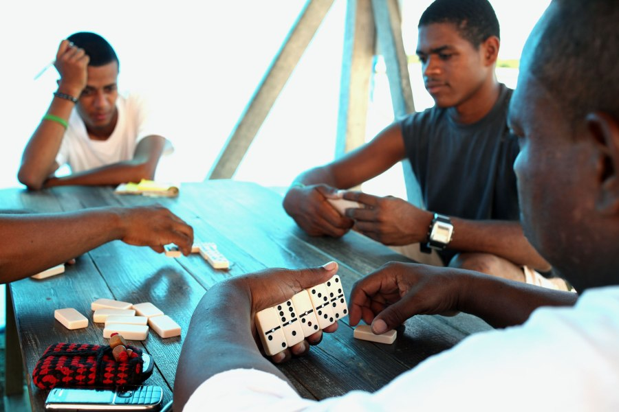 A group of locals concentrates on their game of dominos in the shade next to the only gas station in Placencia Belize. Photo: Alex Washburn