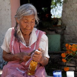 Señora Lopez of Santa Maria del Tule opens a bottle of Carona to place on her son's grave. He passed away three years ago at the age of 29. Photo: Alex Washburn