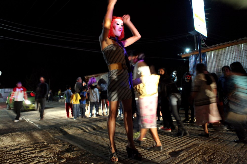 A man dressed in drag dances and poses in the lights of a police vehicle as the residents of Tule Mexico exit the city cemetery following a dance party on November 2, 2013.