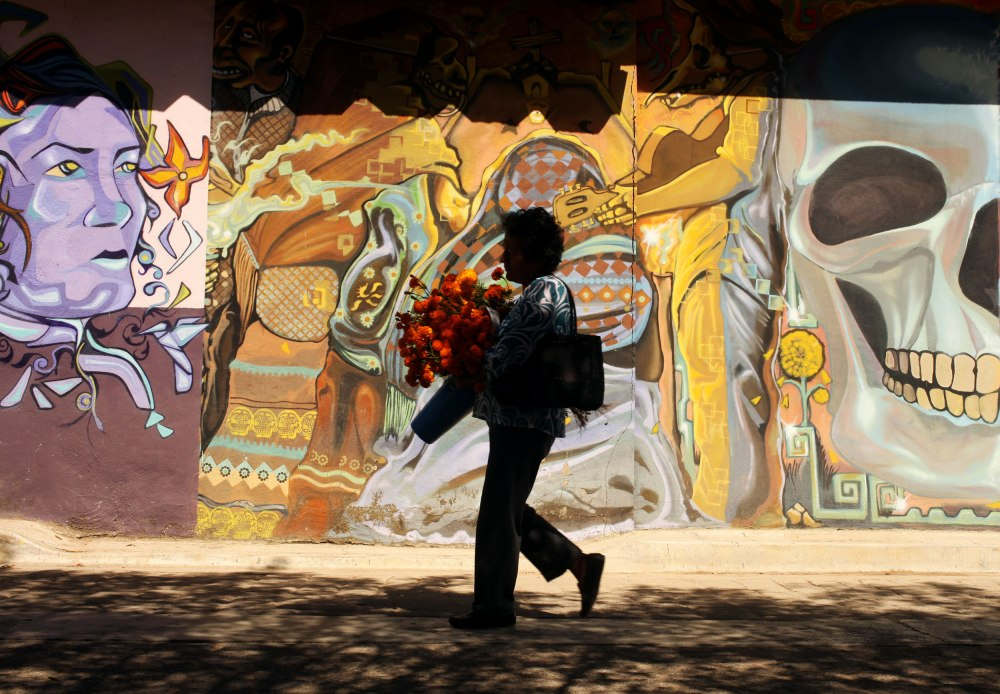 A woman carries marigolds traditionally used for Dia De Los Muertos decorations through the town of Xoxocotlan Mexico. Photo: Alex Washburn