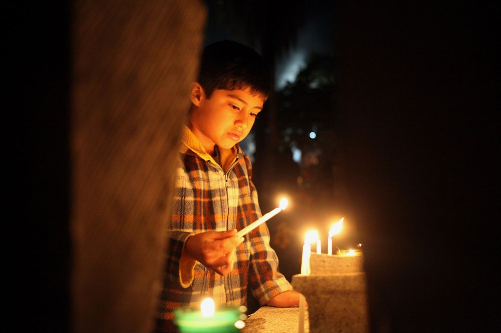 A young boy lights candles with his sister and grandfather in the main cemetery of Xoxocotlan Mexico in observance of Dia De Los Muertos. Photo: Alex Washburn
