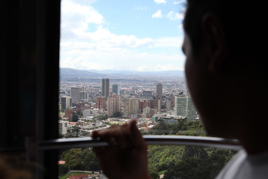 A man looks out over Bogota Colombia from the Transferico cable car that gives tourists and locals a view of the city from the top of a nearby mountain. Photo: Alex Washburn