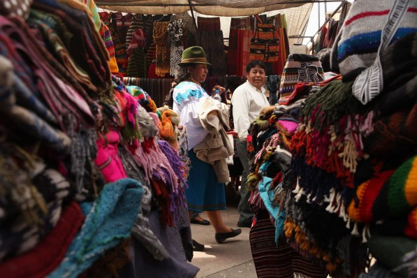 A pair of locals walks through the large market of Otavalo. A lot of local women wear hats similar to this one. Photo: Alex Washburn