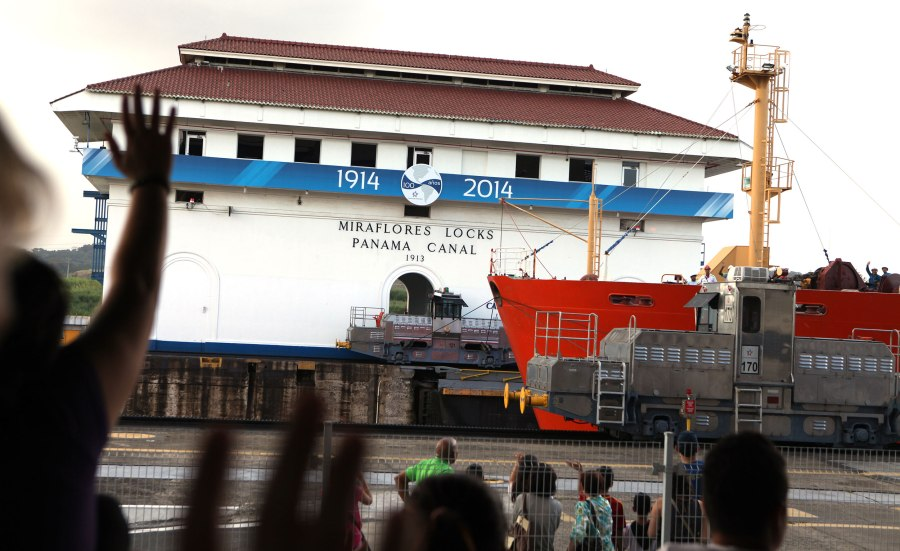 Tourists wave to a ship as it passes through the Miraflores Locks in the Panama Canal. Photo: Alex Washburn