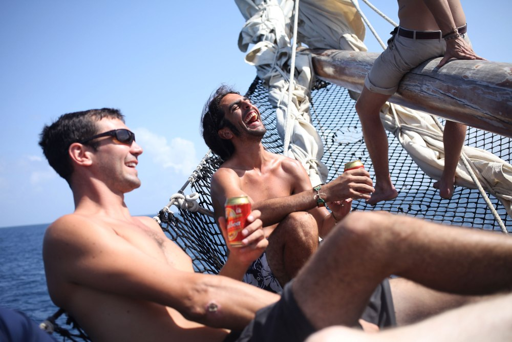 Jesse and Nico laugh at the bow of the ship as we motor out to the San Blas Islands. Photo: Alex Washburn