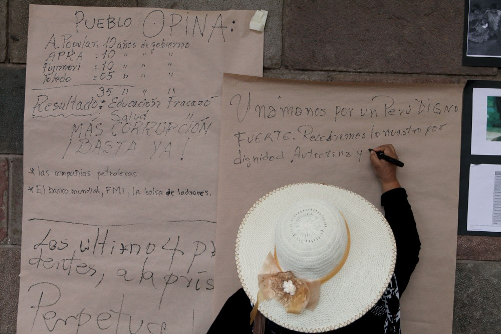 A woman ads her own opinions to a growing list of complaints during a protest against the Peruvian government in Plaza De Armas of Cusco Peru on Tuesday, Feb. 25, 2013. Photo: Alex Washburn
