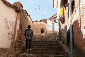 A japanese couple makes their way down a steep alley towards Plaza De Armas in Cusco. Photo: Alex Washburn
