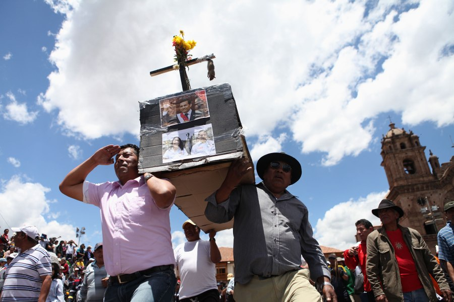 Protestors carry a coffin adorned with Peruvian President Ollanta Humala's name, photos and a dead rat in the Plaza De Armas of Cusco, Peru before setting it on fire on Tuesday, Feb. 25, 2013. Thousands of gathered from various regions of Peru to protest corruption within the Peruvian government and prevented traffic from flowing through the city.  Photo: Alex Washburn
