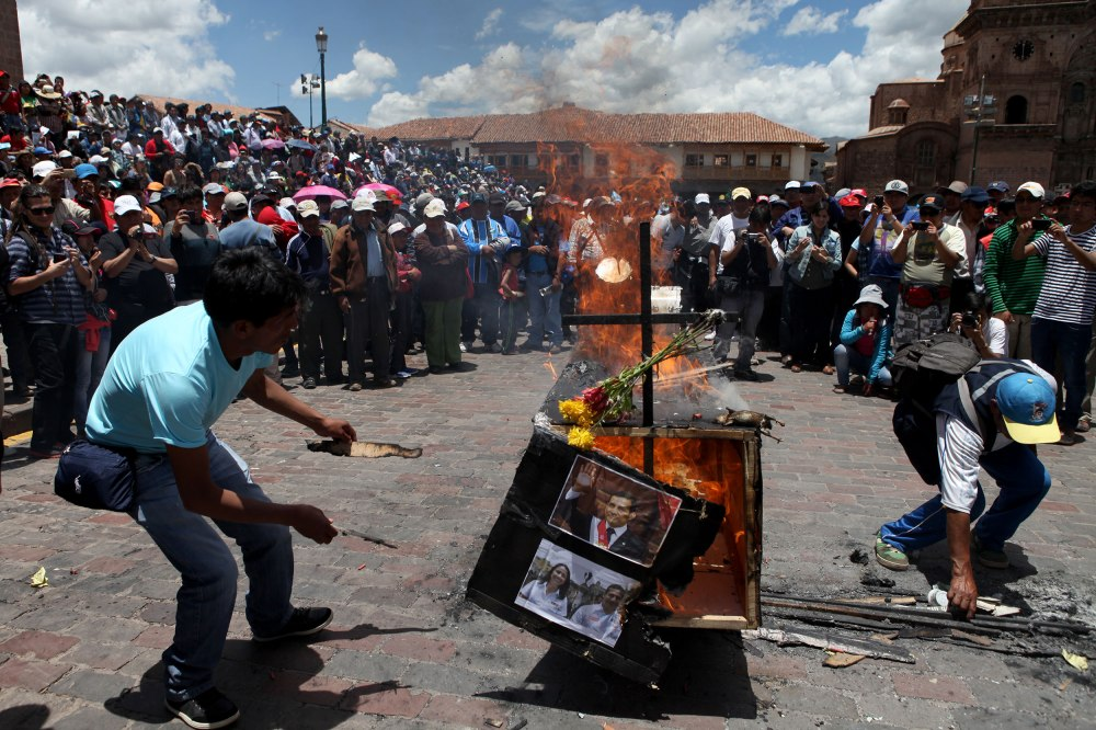 Protestors burn a coffin adorned with Peruvian President Ollanta Humala's name and photos in the Plaza De Armas of Cusco on Tuesday, Feb. 25, 2013. People gathered from various regions of Peru to protest corruption within the Peruvian government and prevented traffic from flowing through the city and greater Cusco region. Photo: Alex Washburn