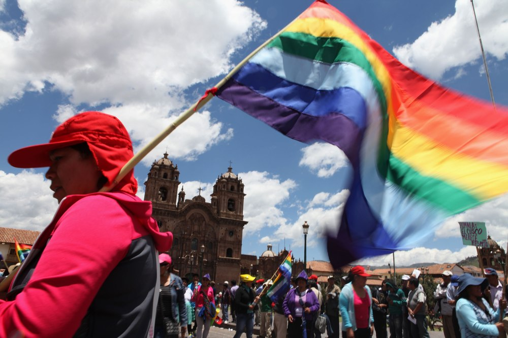 A protestor carrying the city flag of Cusco participates in a demonstration in Plaza De Armas of Cusco, Peru on Tuesday, Feb. 25, 2013. Photo: Alex Washburn