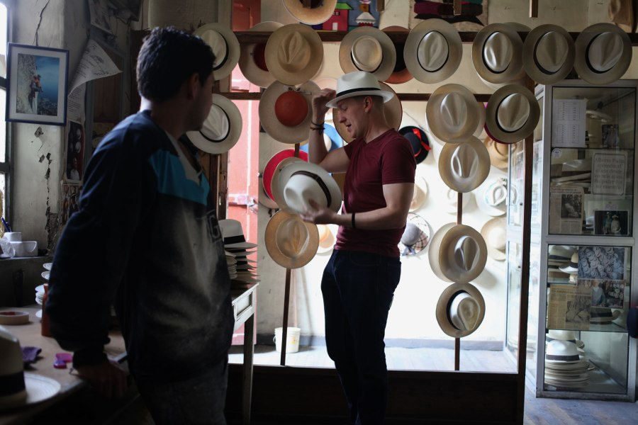 Nathaniel tries on hats trying to determine which one fits best as Juan-Carlos watches and answers questions. Photo: Alex Washburn