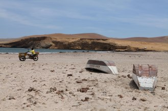 A guy scoots by some overturned fishing boats in La Reserva Nacional De Paracas. Photo: Alex Washburn