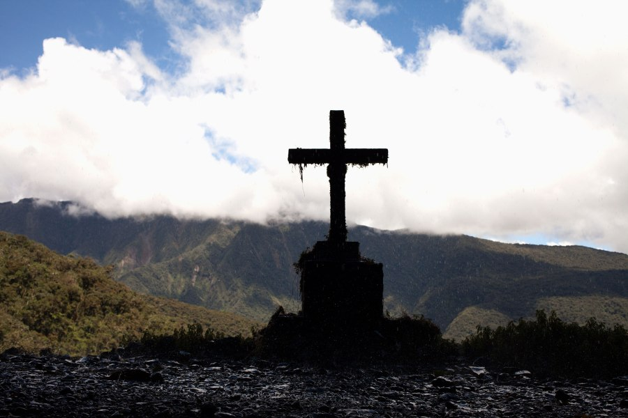 A cross marks where people have died on the Bolivian Death Road near a series of small waterfalls. Photo: Alex Washburn